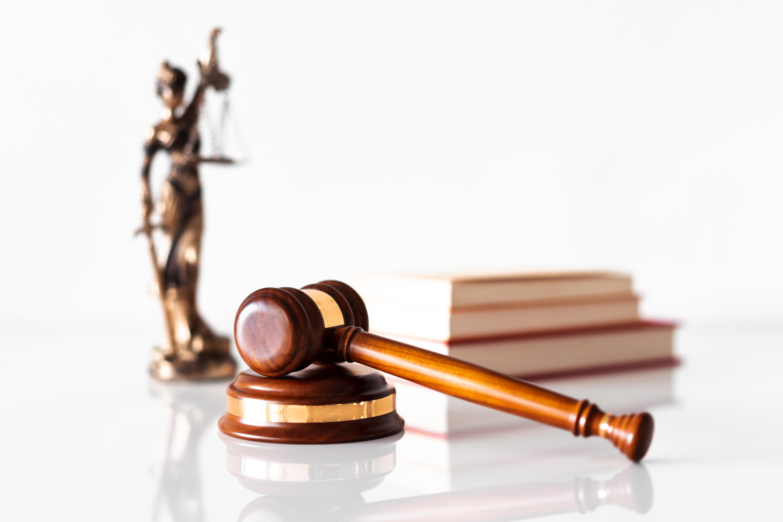 Ein Gerichtsurteil ist gefallen. Ein Hammer und eine Figur von Justizia symbolisieren das.