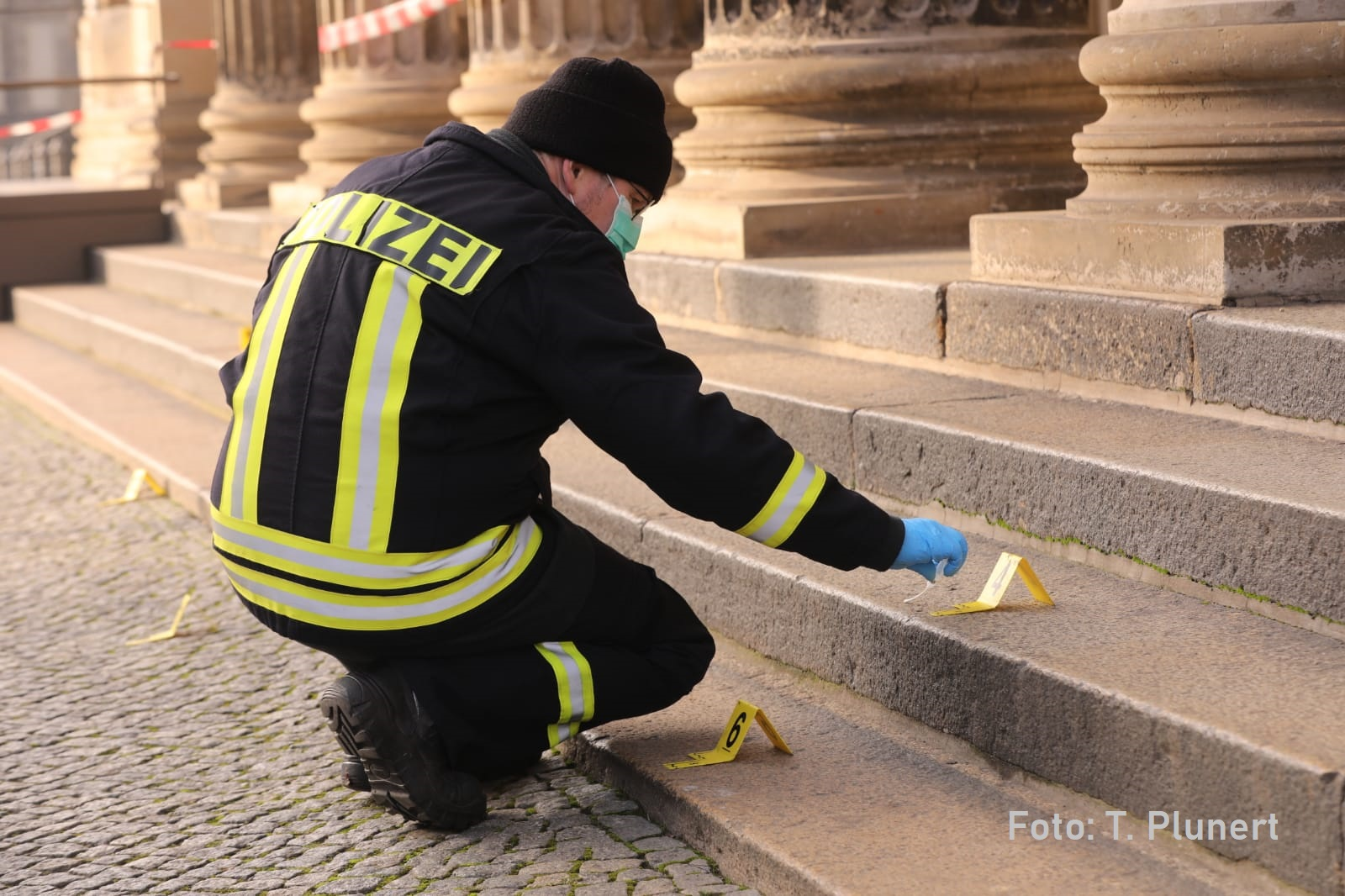 Spurensicherung nach Raub im Grünen Gewölbe in Dresden. Ein Polizist stellt ein gelbes nummeriertes Schild auf einer Treppe an der Schinkelwache auf.