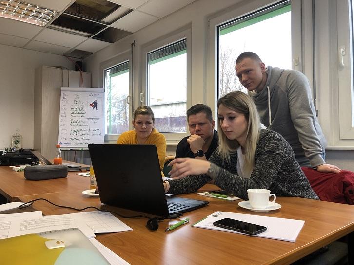 Vier Teilnehmer des Social Media-Workshops bei Andreas Szabó arbeiten zusammen am Laptop.
