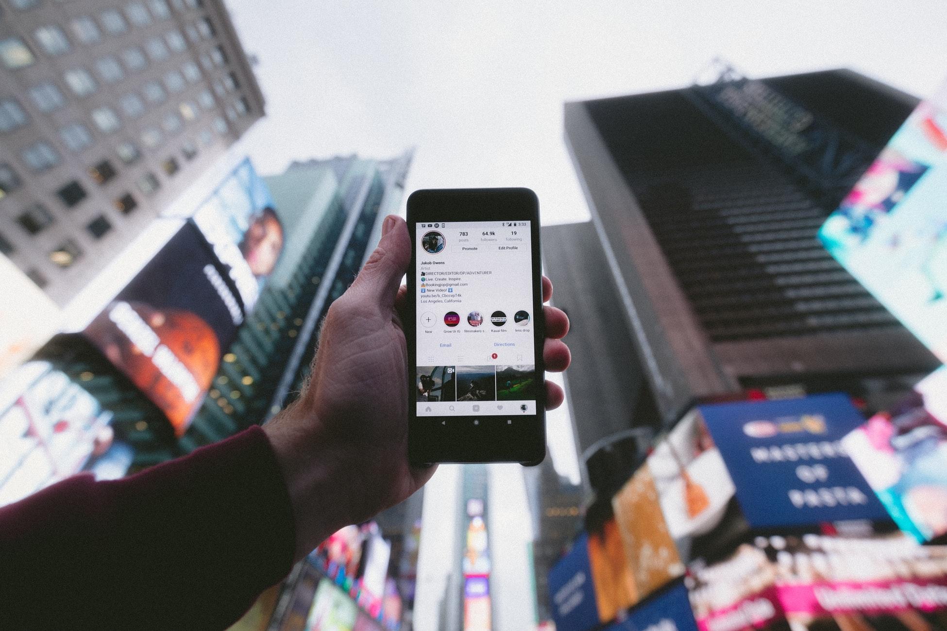 Mehr Reichweite auf Instagram ist Thema im Text. Hier im Bild wird ein Handy mit der Insta-App in den Himmel einer Großstadt gehalten.